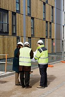 Building contractor and architects in discussion at construction site