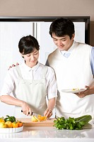 Young couple cooking together in kitchen with vegetable