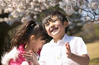 Boy and girl smiling under cherry blossoms, Tokyo Prefecture, Honshu, Japan