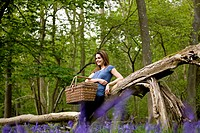 A young woman leaning against a tree, holding a picnic basket (thumbnail)