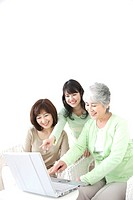 Three generations of women using a laptop