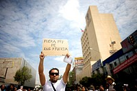 An electrician protests the government's shut down of state-run power company Luz y Fuerza del Centro LFC outside the LFC headquarters, right, in Mexi...