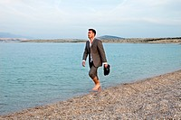 Businessman walking on the beach