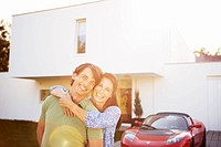 Couple posing in front of house and car