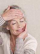 Senior citizen in sport wear stretches her neck