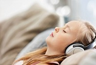 Girl 10_11 laying on backlistening to mp3 player