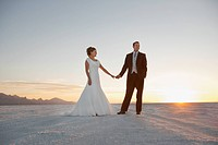 Bride and groom holding hands in desert