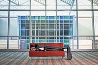 Traveling businessman sleeping on sofa in lobby