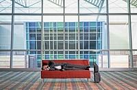 Traveling businessman sleeping on sofa in lobby