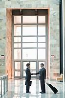 Traveling businessmen shaking hands in building lobby