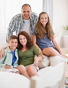 Smiling Hispanic family sitting on sofa together