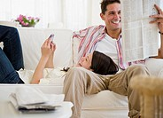 Smiling couple relaxing on sofa together with cell phone and newspaper