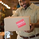 African American deliveryman holding out box with ´fragile´ sticker