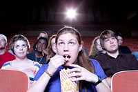 Caucasian woman eating popcorn in movie theater
