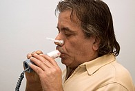 COPD patient. Patient undergoing pulmonary lung function tests PFTs at a clinic for chronic obstructive pulmonary disease COPD. Here they are using a ...