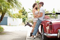 Couple kissing by vintage car