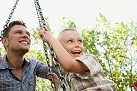 Father pushing son on a swing
