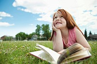 Girl reading book outdoors (thumbnail)