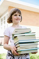 Girl holding stack of books