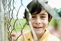 Boy standing by fence (thumbnail)