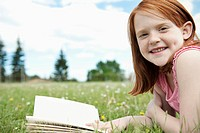 Girl reading book outdoors