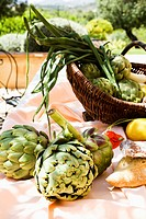 Basket with artichokes, lemon and green onions