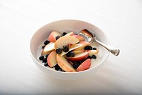 Apple slices and berries in a bowl with milk