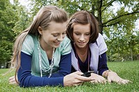 Young women using cell phone on grass