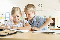 Boy looking at girl's schoolwork in classroom