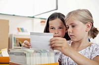 Girls looking at paper in classroom