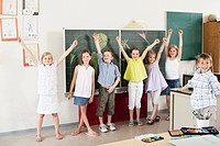 Children with arms raised in classroom