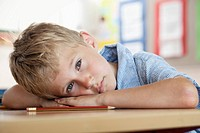 Boy resting on desk in classroom