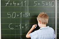 Boy doing arithmetic on blackboard