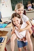 Girl giving friend piggyback ride in classroom