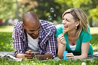 Young couple blowing bubbles