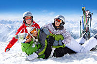 Smiling family of skiers playing in snow on ski slope