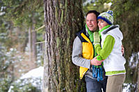 Smiling couple leaning against tree trunk in woods