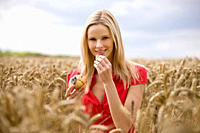 A woman sitting in a wheatfield, eating a blueberry muffin