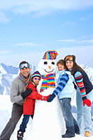 Happy family making snowman together
