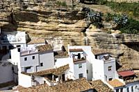 White homes constructed in caves sit under huge rocks in Setenil de las Bodegas village, Cadiz province, Andalusia, Spain