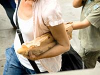 Woman carrying a loaf of bread. Barcelona, Catalonia, Spain.