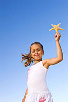 Portrait of girl 8_9 holding up starfish