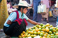Young Burmese woman selling lime fruits at the market, Nyaungshwe, Inle Lake, Myanmar