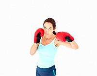 Concentrated hispanic woman with boxing gloves working out against a white background