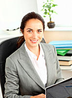 Charismatic young businesswoman using her laptop sitting at her desk in her office