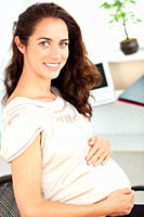 Pregnant businesswoman smiling at the camera sitting at her desk in her office
