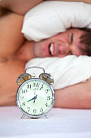 Angry young man lying in bed and annoyed by his alarm clock in the bedroom at home