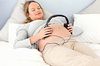 Happy future mom putting headphones on her belly lying on a bed