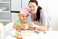 Cute daughter and mother showing a cookie in form of a man to the camera