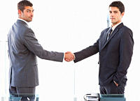 Two charismatic businessmen shaking hands standing in the office at work
